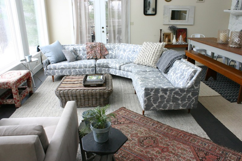 vintage sofa table grey corner sofa mediterranean rug area rug black side table armchair pillows windows wall mirror black tray rattan table