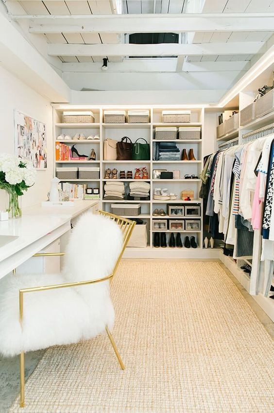 waling closet, brown rug, white table with golden chair, white faux fur, shelves on one side of the wall, rails and shelves on the other