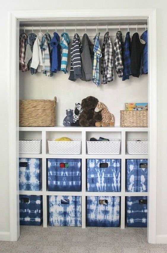 walking closet behind white wall and arch with rail to hang clothes, shelves with boxes