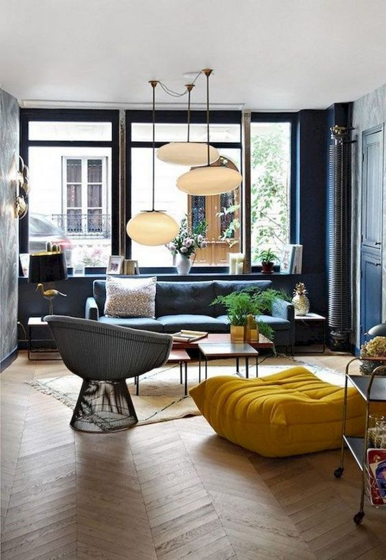 warm living room, chevron wooden floor, blue wall, large glass window, pendants, blue sofa, yellow ottoman, black wire chair, low side table
