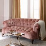 Warm Pink Tufted Sofa With Tufted Back And Seating, Gass Coffee Table, Grey Rug, Wooden Floor, Yellow Curtain