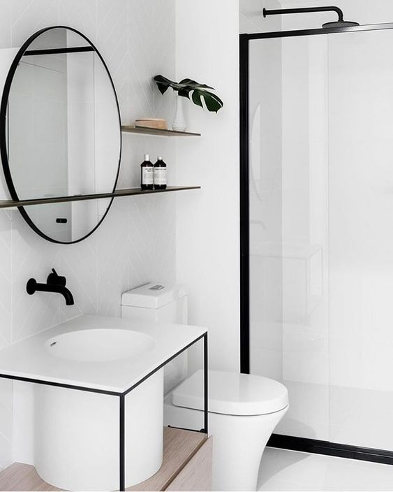 white bathroom, white floor and wall, clear glass partition, white toilet, white square vanity with round sink seen under, round mirror, black shower, black floating shelves