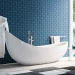 White Bathtub With One Corner Higher Than The Other, Blue Wall Tiles, Wooden Floor