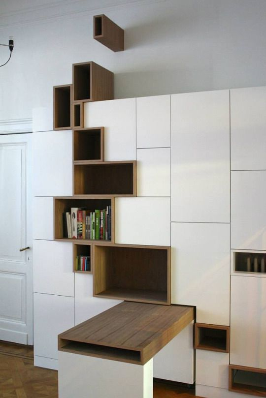 white cabinet with dark brown shelves along the body from the bottom to the wall above the cabinet, sliding table
