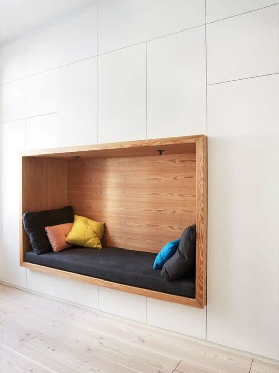 white cupboard with nook, wooden seating and side protruded, pillows, ceiling lamp