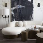 White Curvy Sofa With Copper Support, Copper Round Coffee Table, Copper Stool, White Wall, Wooden Floor
