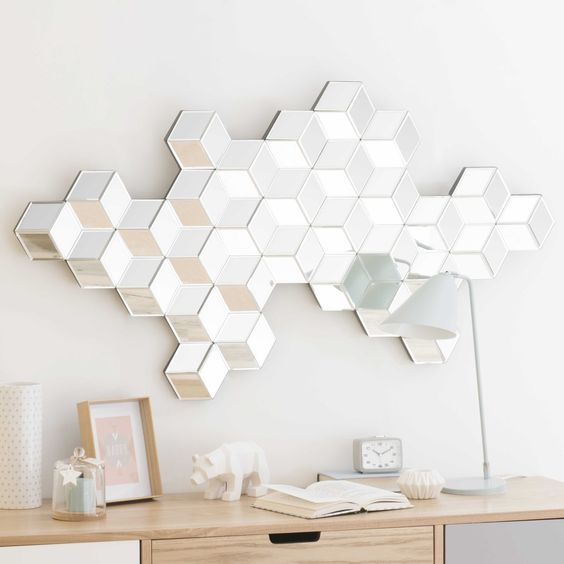 white hexagon mirror with 3D effect, above wooden cabinet, table lamp