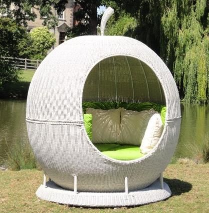 white rattan apple shaped bench with green cushion and pillows