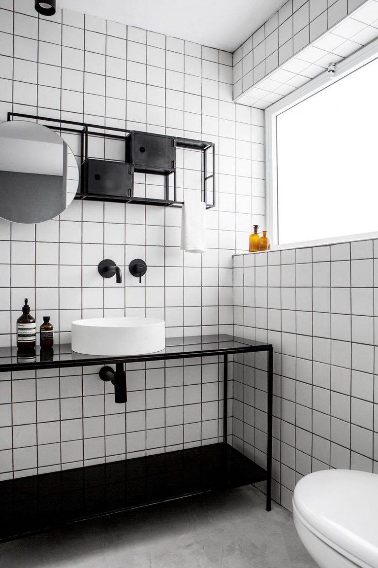 white square tiles on the wall, marble floor, black shelves vanity, black floating shelves, white round sink, round mirror, white toilet