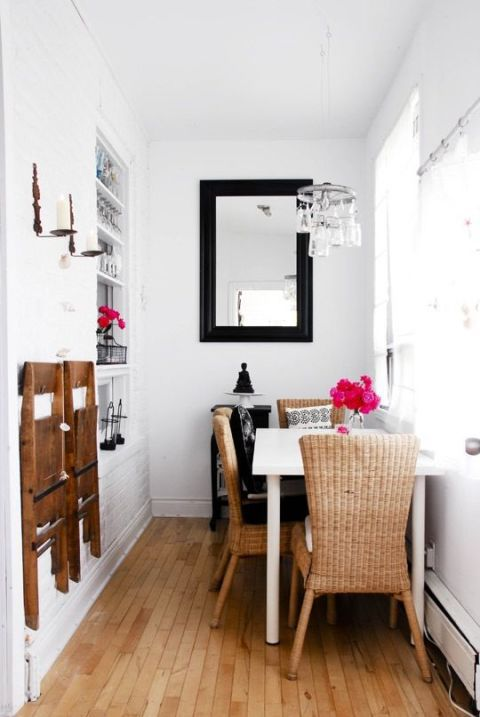 white wooden table, rattan chairs with tall back, wooden floor, white wall, small chandelier