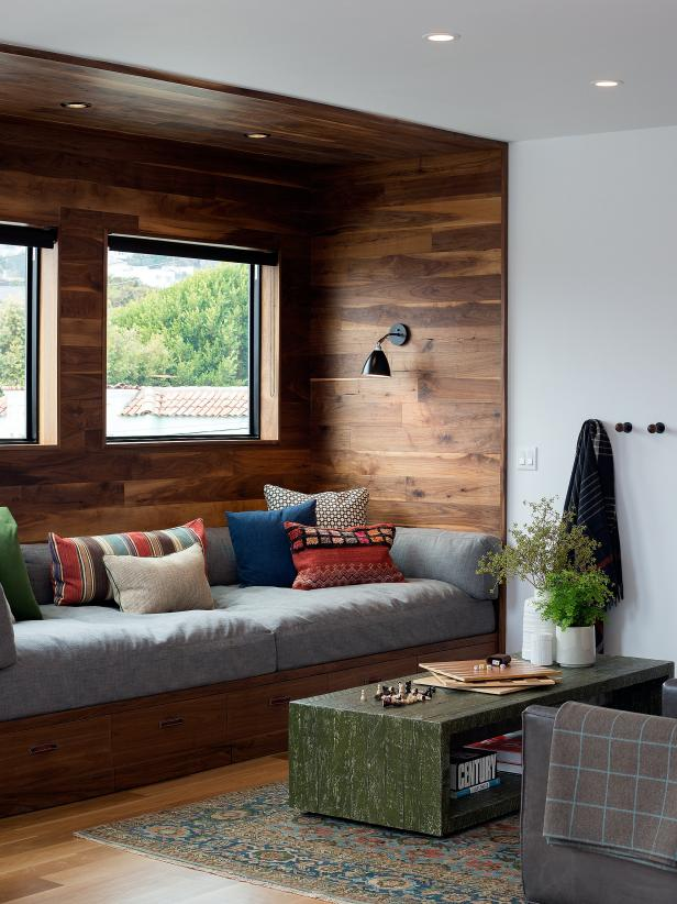 window seat, dark brown wooden layered wall, small window, wooden bench, grey cushion, pillows, black sconce