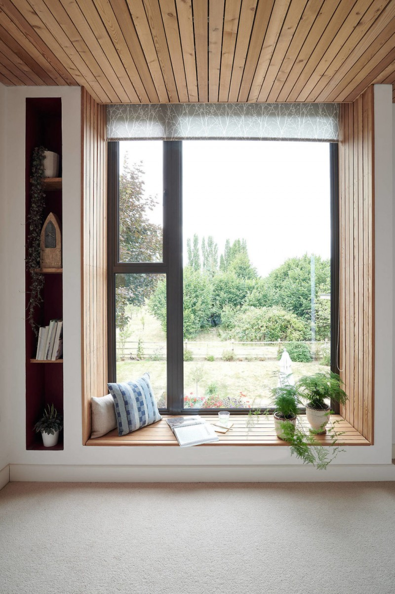 window seat, low and large window, wooden planks layered, wooden ceiling, narrow shelves on the side