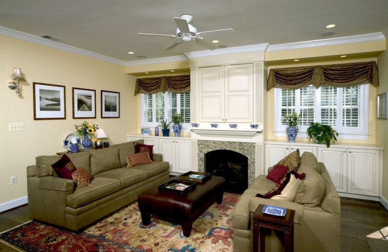 window swag valances white ceiling fan fireplace brown leathered ottoman greeen sofas red pillows mediterranean rug wall sconce cabinet window shutter