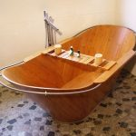Wooden Boat Shaped Baht Tub With Wooden Board Across, On Marble Floor