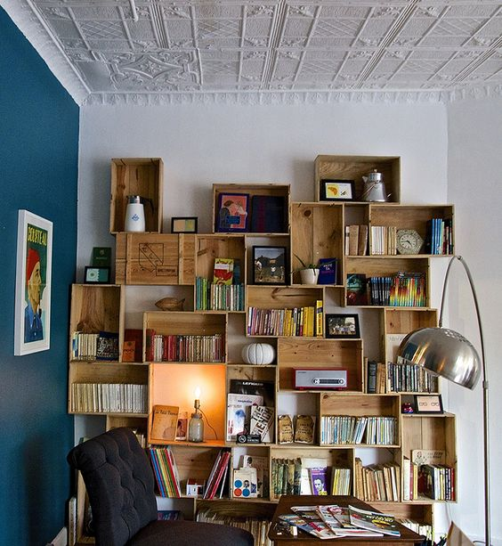 wooden crates for bookcase supported on the wall on study room with wooden table, black chair, floor lamp