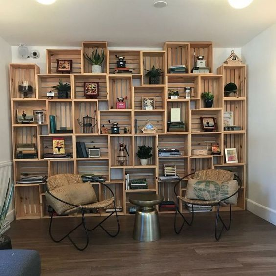 wooden crates stack tidily to the wall with books, decorations, plants, wooden floor, round chair with leather seating, metal coffee table