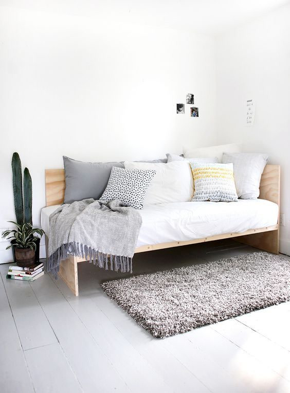wooden daybed with cornered back, white cushion, pillows, grey rug