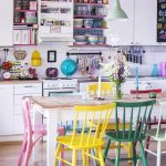 Wooden Dining Table With Colorful Wooden Chairs, Wooden Floor, White Upper And Bottom Cabinet In The Kitchen, White Backsplash Tiles, Green Pendant