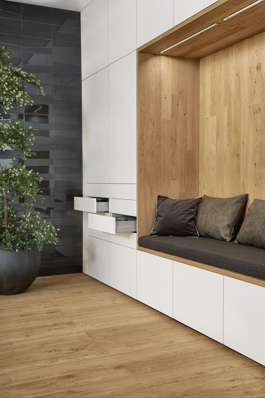 wooden nook with dark grey cushion, pillows, ceiling LED lights, white cupboard with dreawers