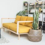 Wooden Sofa With Yellow Cushion, White Floor, Rattan Basket, Shelves, Black Crate Table.