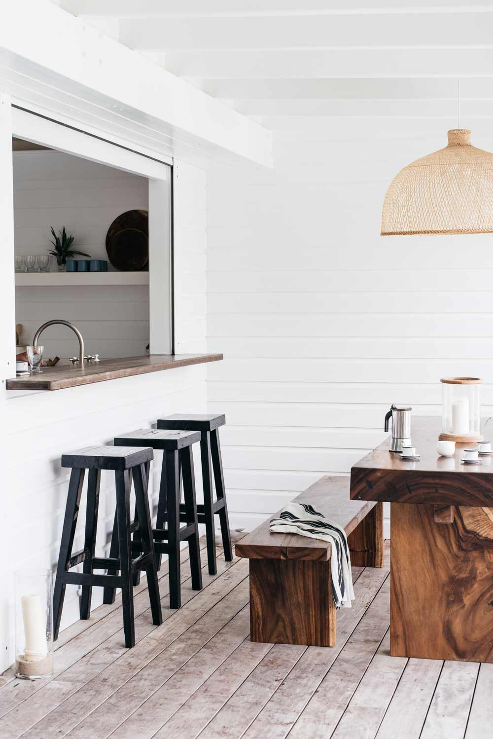 wooden terrace, wooden floor, white wooden wall, open kitchen, black wooden stools, brown wooden table and bench, rattan pendant