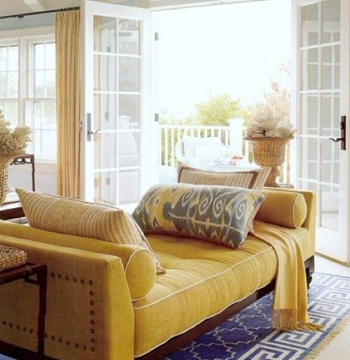 yellow sofa bed with round pillow on both ends, tufted details