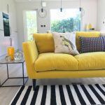 Yellow Sofa With Black Legs, Wooden Floor, Striped Rug, Side Table, White Wall, Round Pendants