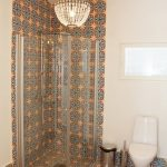 Bright Patterned Tiles On The Wall And Floor, White Wall And Floor, White Toilet, Chandelier, Glass Shower Partition