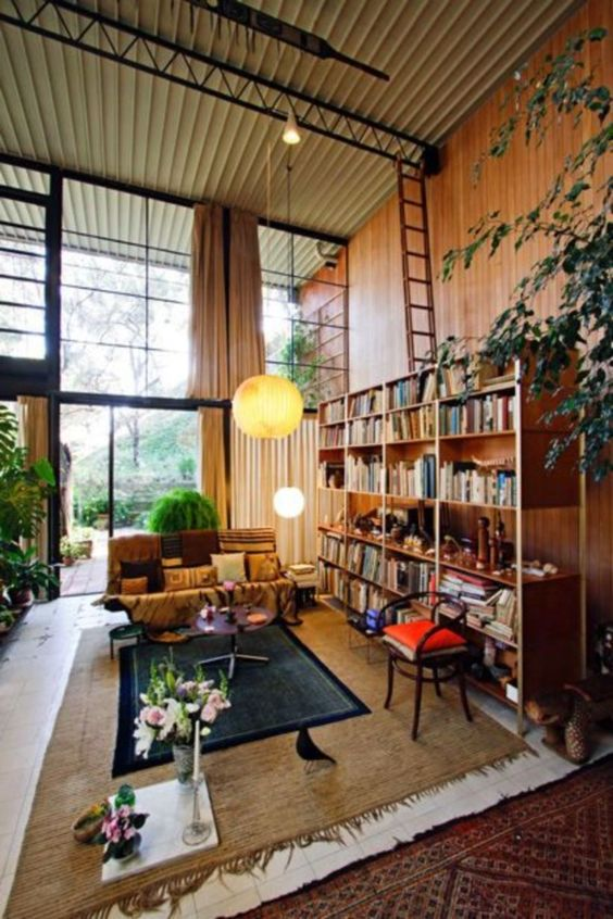 07 tall living room, brown floor, brown rug, brown sofa, chair, wooden booksheles, wooden wall, yellow white pendant