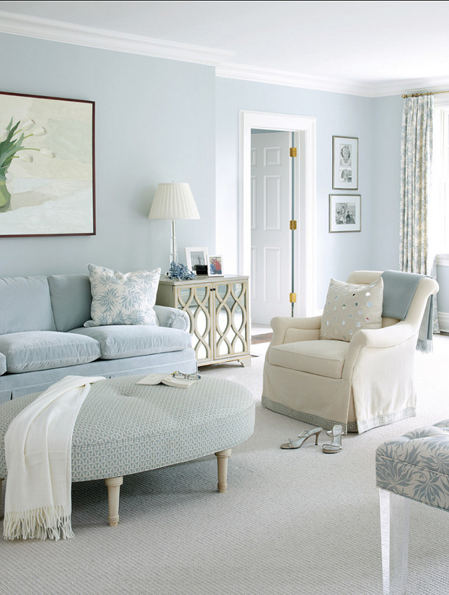 living room, white rug, soft blue sofa, soft blue ovale ottoman, white chair, soft blue wall, white table lamp