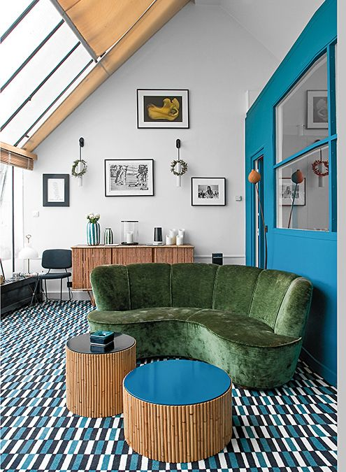 10 living room, blue white rug, green velvet sofa, round wooden coffee table, white wall, wooden cabinet, black chair, blue partition, sloping glass ceiling