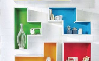 Colorful floating tetris shelves on white brick wall