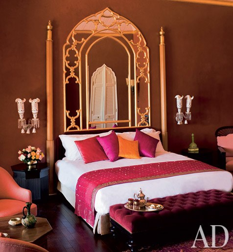 Moroccan arch mirror with details on the frame in bedroom's wall, wooden floor, white sconces, black wooden side table, pink chairs, wooden coffee table, purple tufted bench