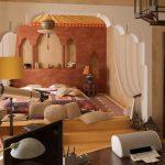 Moroccan Bedroom, Wooden Floor, Bed On The Floor, Brown Wall With Moroccan Archs, Moroccan Arch, Yellow Lamp, Moroccan Pendant, Patterned Bedding