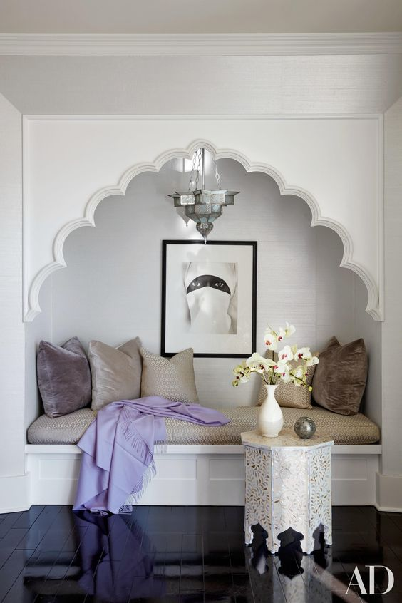 Moroccan reading nook, white built in bench, beige cushion, beige pillows, silver pendant, black glossy wooden floor, white side table with moroccan carvings