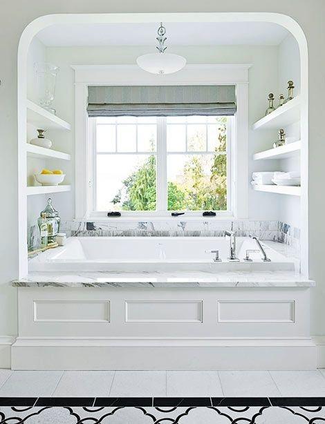 alcove, white wall, white floating shelves, white marble top, white tub, white black patterned floor bathroom floor