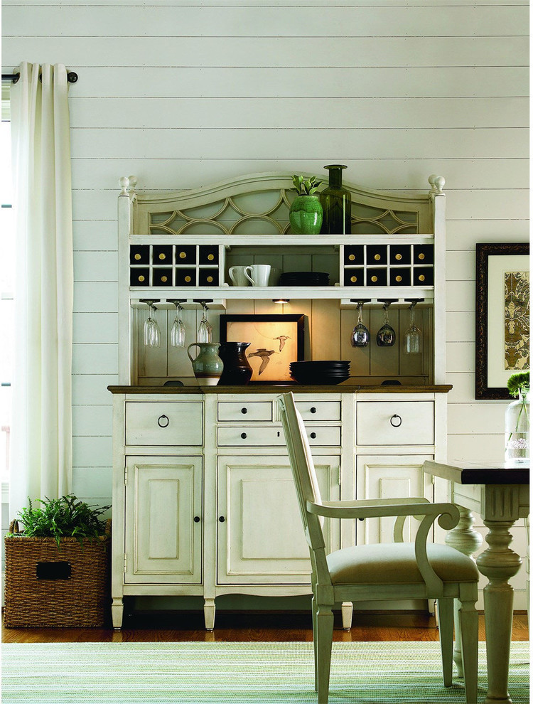 bar server furniture white wooden wall white curtain green rug white wooden dining table white chairs frame wine rack wine glasses plates rattan baskets white drawers