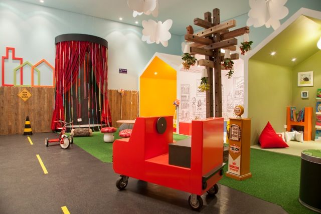 basement, grey floor, green mat, blue wall, boxes shaped like house, wooden car with wheel
