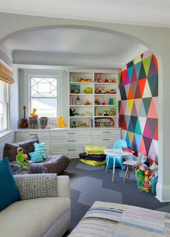 basement, grey floor, white wall, colorful wall, white built in shelves and drawers, white sofa, ottoman, lounge chair, low study set