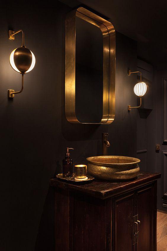 bathroom, brown floor tiles, wooden cabinet, golden sink, golden mirror, golden sconces
