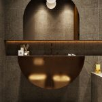Bathroom, Brown Tiles On Wall And Floor, Dented Middle Shelves, Mirror, White Bulb Sconces, Golden Cabinet In Crescent