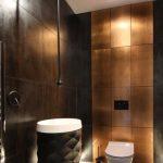 Bathroom, Dark Grey Floor, Dark Grey Wall Tiles, Dark Acorn Shaped Vanity And White Sink, White Toilet, Golden Statement Wall
