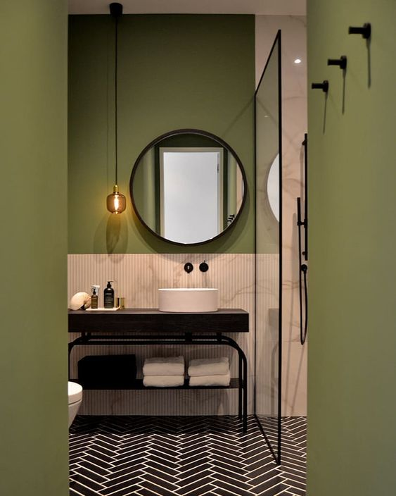 bathroom, green wall, blck herringbone floor tiles, pink wall tiles, dark wooden table with white sink, round mirror, long and thin pendant