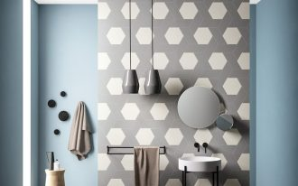 bathroom, grey floor tiles, blue painted wall, wall partition with pattern tiles, grey pendants, white sink black support, black rail, round mirrors