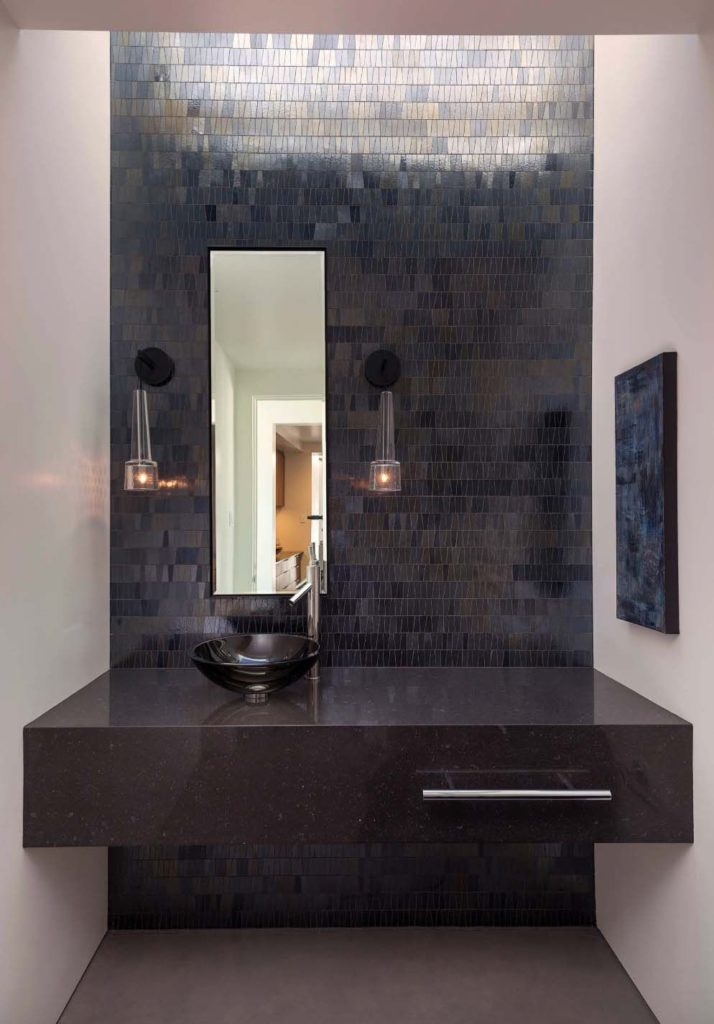 bathroom, grey floor, white wall, black wall mosaic tiles, black marble floating vanity, black round sink, sconces
