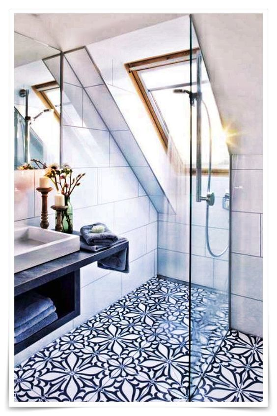 bathroom, sloping ceiling, white wall tiles, white and black patterned floor tiles, black floating vanity with sheles, grey sink, mirror, glass window