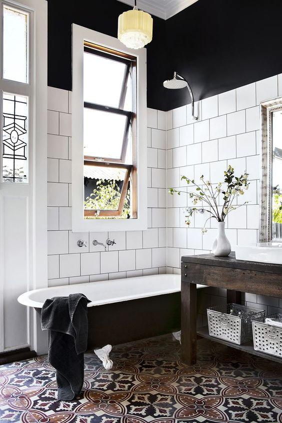 bathroom, warm brown black patterned tiles, black tub, dark wooden table, white wall tiles, black wall, shower, yellow pendant
