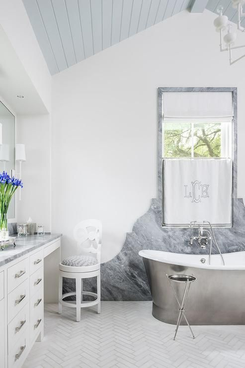 bathroom, white herringbone floor tiles, white wall, grey marble on the wall and window frame, white cabinet with grey top, grey wooden ceiling