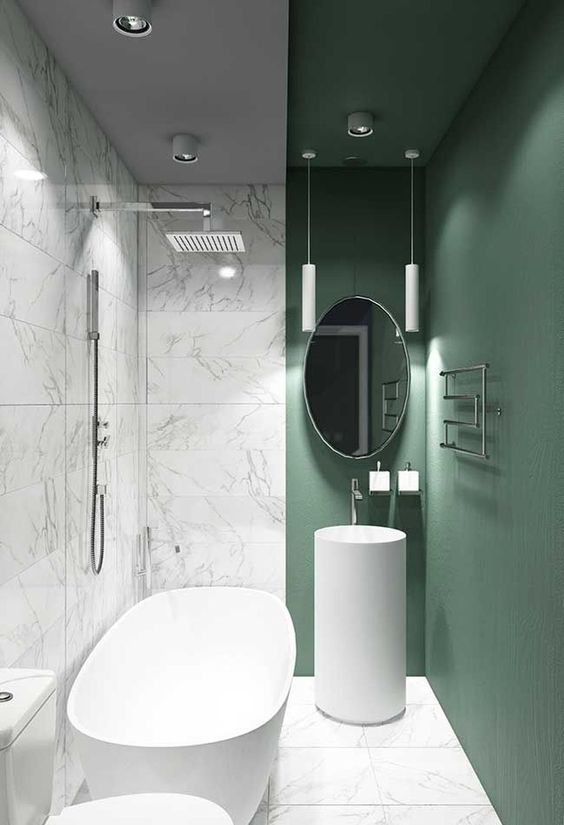 bathroom, white marble floor, white marble wall, green painted wall and ceiling, white pendant, oval mirror, white tall round sink, white tub, white toilet
