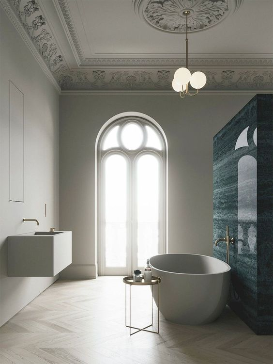 bathroom, wooden chevron floor tiles, white tub, side table, floating white vanity, white ceiling with details, bulbs pendant, blue marble wall partition